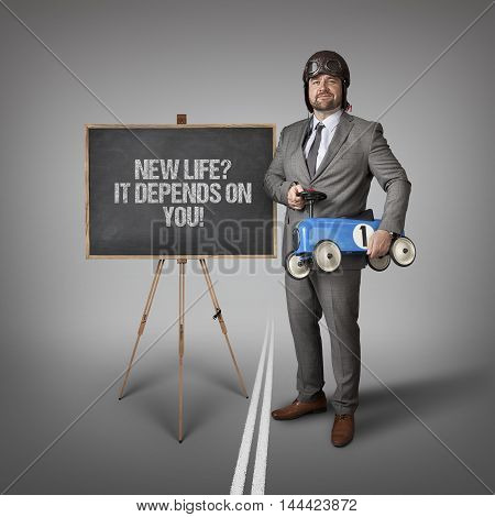 New life it depends text on blackboard with businessman and toy car
