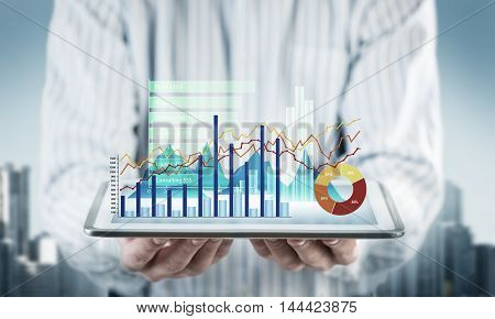 Close view of businessman with tablet and graphs and charts on screen