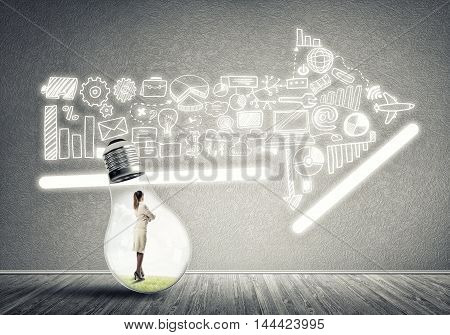 Businesswoman inside of light bulb in empty concrete room looking at arrow made up of business icons