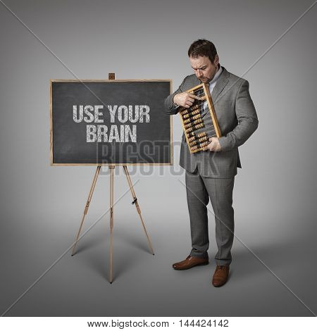 Use your brain text on blackboard with businessman and abacus