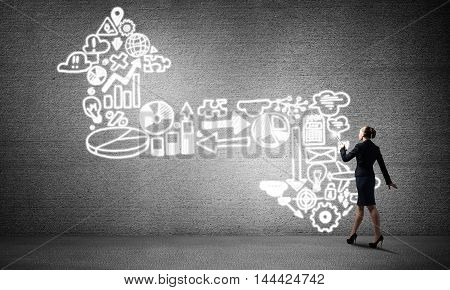 Young elegant businesswoman with flashlight in concrete room and arrow made up of business icons.