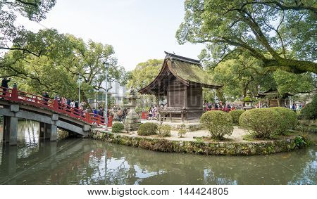 Fukuoka, Japan - March 19, 2016: Fukuoka on March 19, 2016. People are crossing the famous red bridge of Dazaifu shrine.
