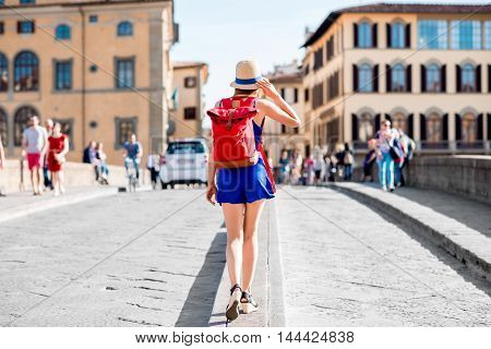 Beautiful female traveler in blue dress, hat and backpack walking on crowded Holy Trinity bridge in Florence city. Back view