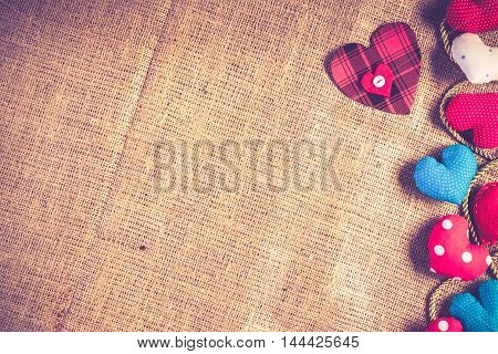 Handmade love hearts on brown burlap fabric background with place for your text.
