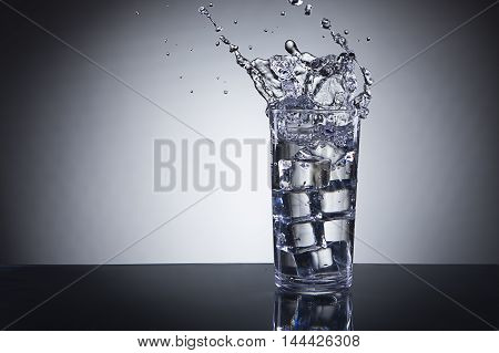 Ice dropped in water glass. Ice being dropped into a glass of water making a splash.