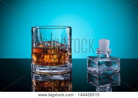 A close up of a glass of liquor with the bottle stopper.