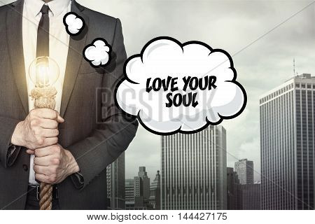 Love your soul text on speech bubble with businessman holding lamp