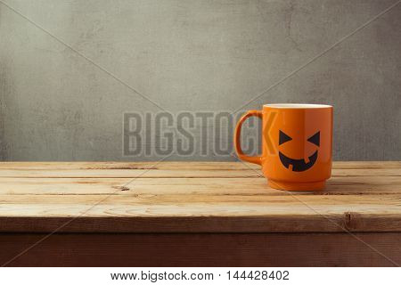 Coffee cup as jack o lantern pumpkin on wooden table. Halloween concept