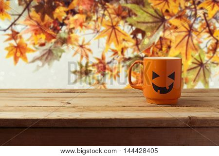 Coffee cup as jack o lantern pumpkin on wooden table over autumn background