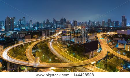 Aerial view highway interchanged with city downtown background at twilight
