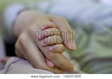 Newborn baby holding his mothers hand selective focus