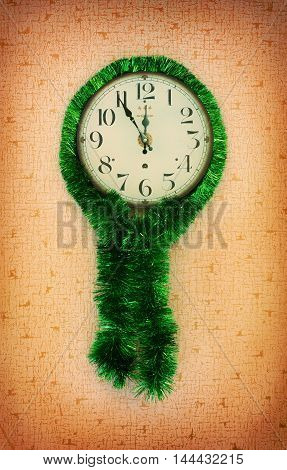 at five minutes to twelve on the old wall clock decorated with green tinsel. the concept of a new year Christmas