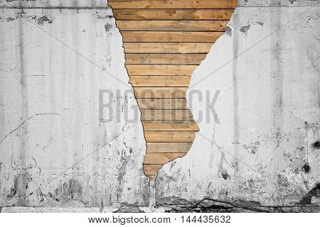 Cracked concrete wall with wooden planks underneath. Rough surface. Cement and wood. Textured background.