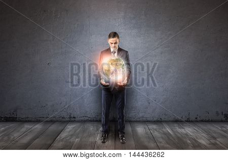 Front view of a businessman holding glowing Earth in his arms. Unlimited possibilities. Global communication. Planet protection. Ecological problems.
