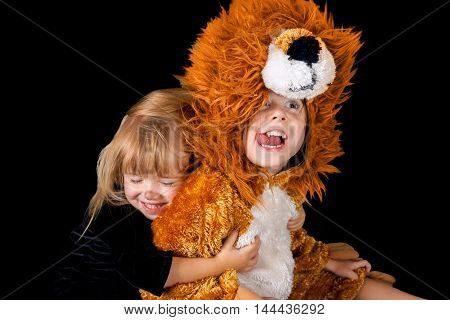 Two sisters in costumes being cute and silly. A little blond cat hugs her older sister the lion. The lion has her tongue out and is making a funny face.