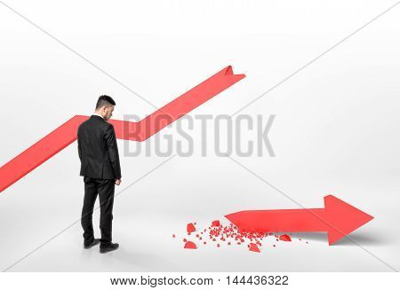 Back view of a businessman looking at broken arrow that fall off the graph. Financial problems and troubles. Stock market collapse. Lose money. Economic crisis.