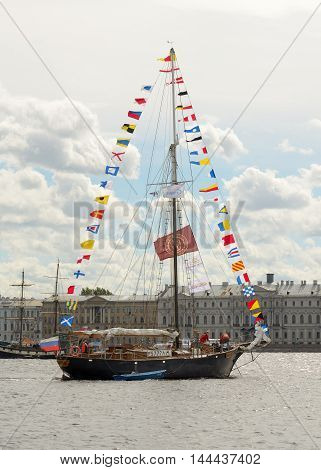 13.08.2016.Russia.Saint-Petersburg.Sailboat on the river with lots of flags on the mast.