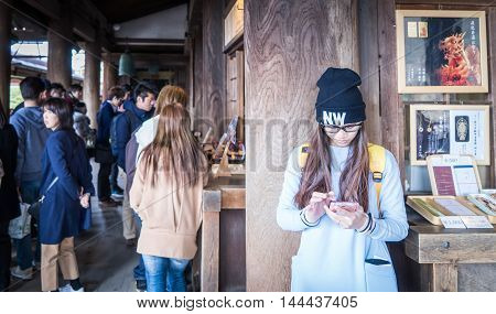 Kyoto, Japan - March 13, 2016: A Japanese teenager is playing with her cell phone in a temple.