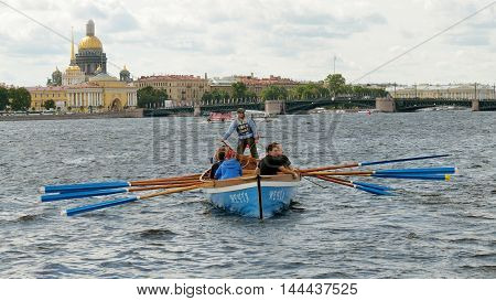 13.08.2016.Russia.Saint-Petersburg.Team of rowers in a boat approaching the shore.
