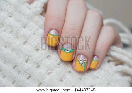 Beautiful female hand with warm yellow nail design.
