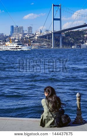 Istanbul Turkey - March 10 2013: View of the European side of Istanbul from the Bosphorus. On the shore watching a woman views. The Bosphorus Bridge (Turkish: Bogazici Koprusu) also called the First Bosphorus Bridge is one of two suspension bridges spanni