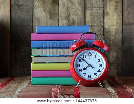 Red retro alarm clock and stack of books. Back to school. Still life with books.