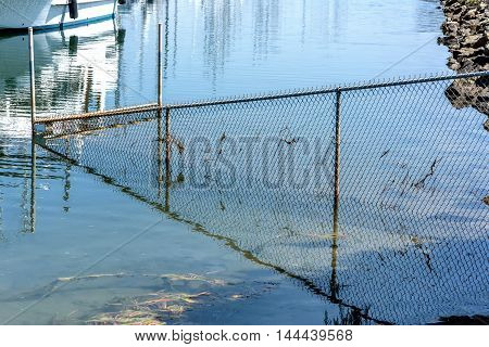 bay wire mesh fence partly drowned in water and its reflection