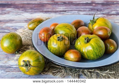 Freshly picked tomatoes in a metal bowl on the old wooden table.