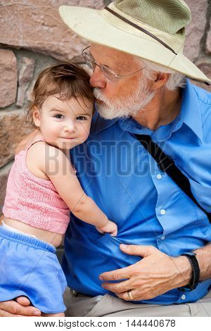 A grandfather kisses his toddler granddaughter on the head as she smirks for the camera. It is a hot day and they are a bit sweaty.
