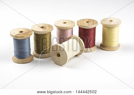 A row of wooden spools with colored thread