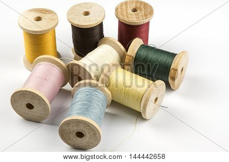 Wooden  spools with colored sewing thread on white
