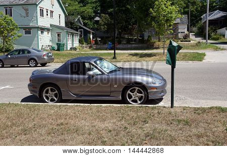 PETOSKEY, MICHIGAN / UNITED STATES - AUGUST 5, 2016: A small Mazda convertible sports car is parked near downtown Petoskey.