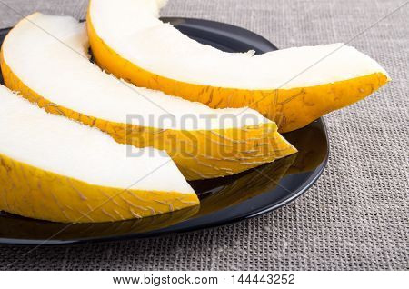 Cut Into Pieces Yellow Melon On A Black Plate