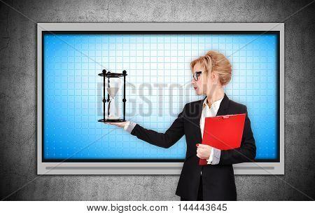 Businesswoman holding sandglass. Blank plasma panel on concrete wall