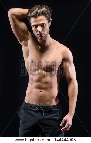 Sexy macho is standing and raising arm behind head. He is looking forward with desire. Isolated on black background