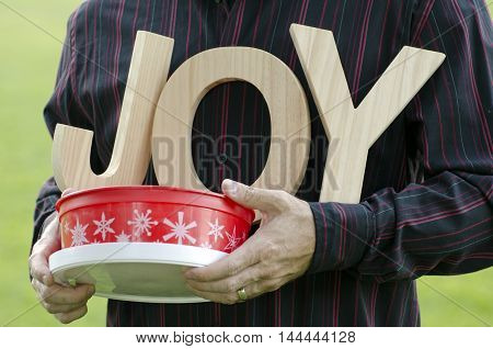 Wooden letters of the word joy - close up of man's hands holding the word with a Holiday themed red plastic container.