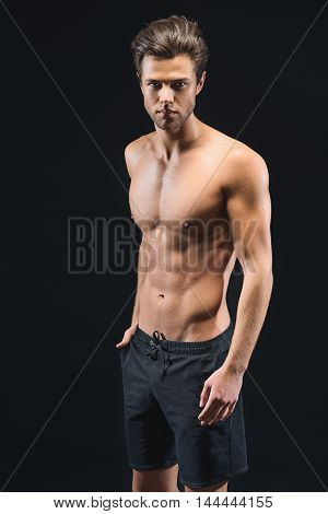 Confident young man is standing and keeping hand in pocket. He has muscular naked torso. Isolated