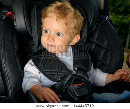 Infant boy 8 months old in a safety car seat.