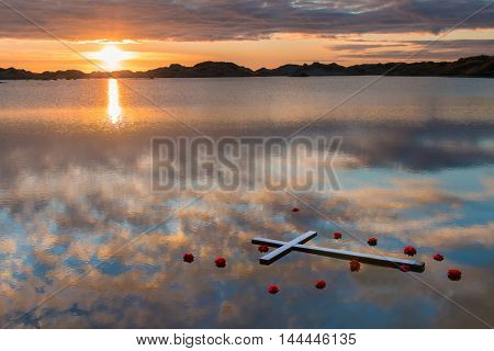 White cross with red flowers around it floating in reflection water.