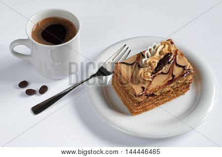 Honey cake with cream and cup of hot coffee on white background