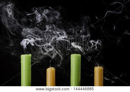 Extinguished candles with smoke on dark background.