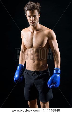 Serious young boxer is standing with boxing gloves. Man is looking at camera with confidence. Isolated on black background