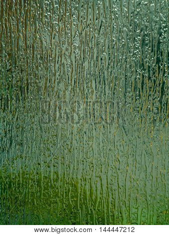 Green textured glass background suggestive of water, plants, forest or grass.
