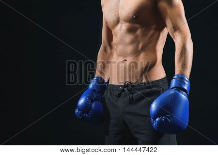 Fit young man is standing with boxing gloves. Close up of his muscular naked torso. Isolated and copy space in left side