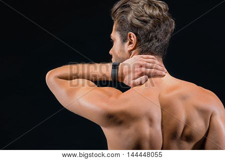 Young man feels pain in his neck. He is standing and massaging it with concentration. Focus on his muscular naked back. Isolated on black background