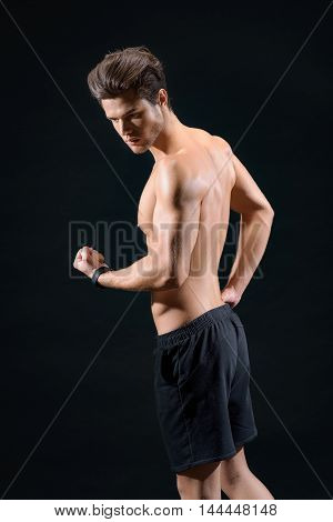Professional male athlete is flexing muscles. He is standing and raising arm with confidence. Isolated