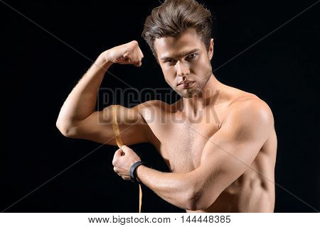Confident young man is taking measurements of his muscles. He is holding tape over arm and looking at camera with satisfaction. Isolated