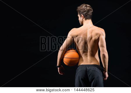 Healthy male athlete is carrying orange ball. He is standing and showing his muscular naked back. Isolated and copy space in left side