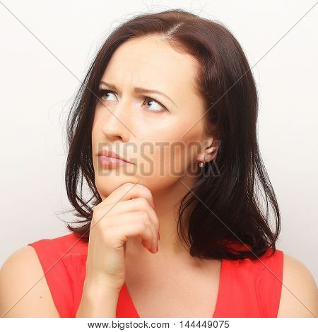 Thinking woman. Young beautiful lady over white background