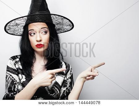 pretty young brunette witch with black hat, isolated against white background